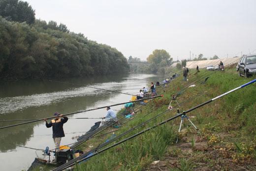 Pescatori sulle rive del fiume Volturno, in Campania, gettano l'amo per pescare cavedani.